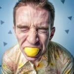 レモンを口に入れて我慢している男性