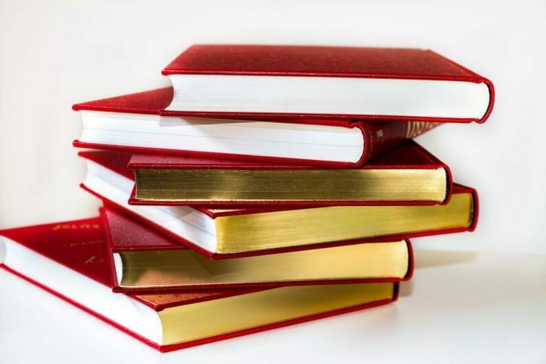 積み重なる分厚い本-カウンセリングの参考書をイメージ
