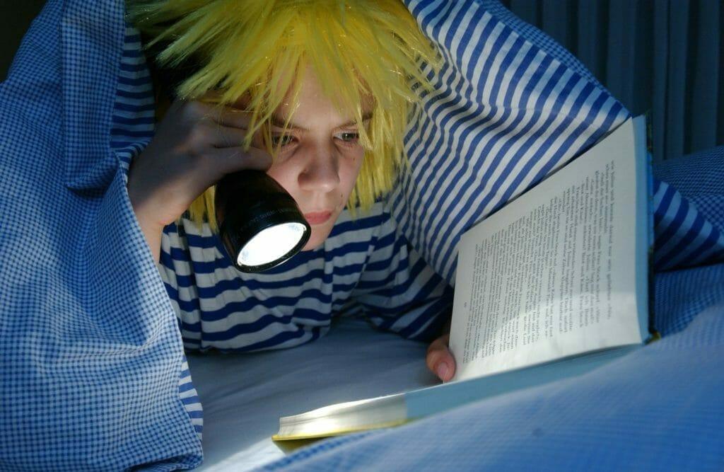 夜更かしをして読書をする少年